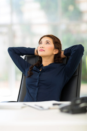 woman looking up: thoughtful businesswoman sitting in office daydreaming