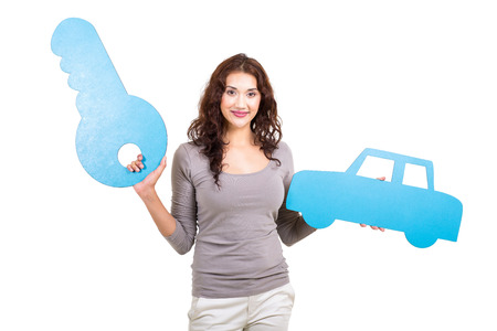 pretty young woman holding paper car and key symbol isolated on white photo