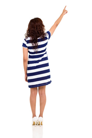 back view of young woman pointing up isolated on white background photo