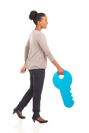 side keys: side view of young african woman walking with a huge toy key  Stock Photo