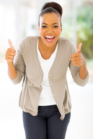 cheerful african woman giving two thumbs up as sign of approval photo