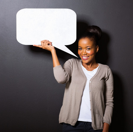 girl holding sign: smiling african american woman holding paper speech bubble Stock Photo