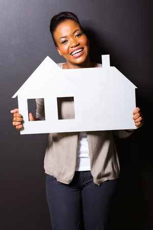 cheerful african girl holding paper house on black background photo
