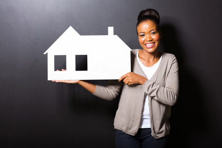 happy african american woman showing house symbol over black background photo