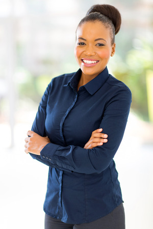 happy afro american businesswoman with arms crossed in office photo
