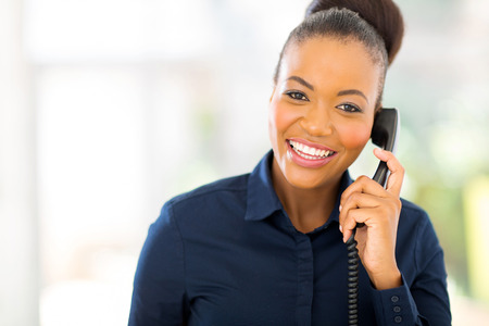 attractive african businesswoman using landline phone photo