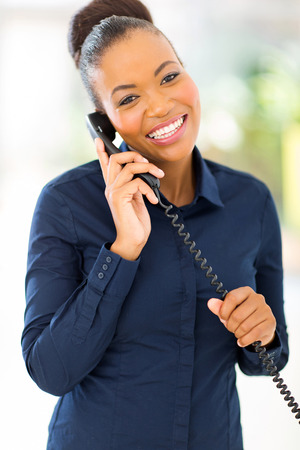 happy african office worker talking on telephone in office photo