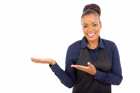 beautiful young african american waitress presenting empty copy space on white background Stock Photo