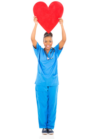 black nurse: cheerful african american female doctor holding heart on white background Stock Photo