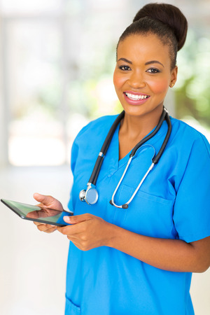 pretty african healthcare worker using tablet computer photo