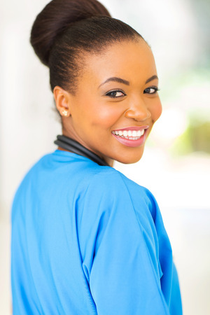 cheerful young african american doctor looking back photo