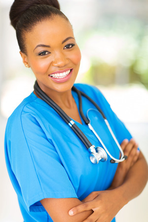 attractive afro american female doctor with arms crossed in hospital photo