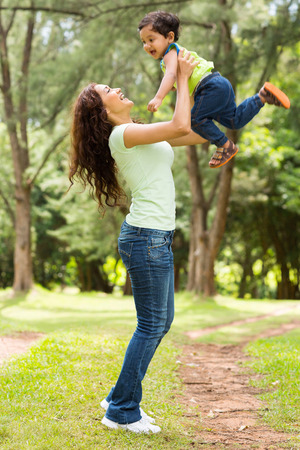 indian people: beautiful young indian woman playing with baby boy outdoors Stock Photo