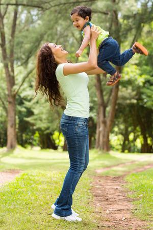 mamma e figlio: giovane e bella donna indiana che gioca con il bambino all'aperto