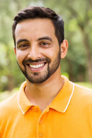 orange man: happy young indian man outdoors looking at the camera