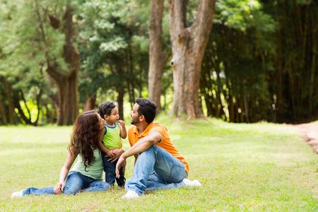 familias jovenes: joven familia de tres sentados juntos al aire libre