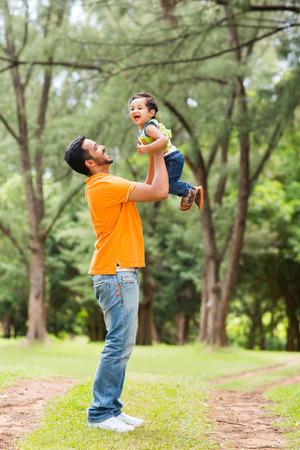 padre e hijo: padre joven feliz jugando con el hijo al aire libre