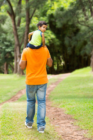 cute little boy sitting on fathers shoulders outdoors photo