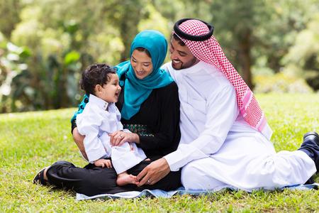 陽気なイスラム教家族は屋外に座って