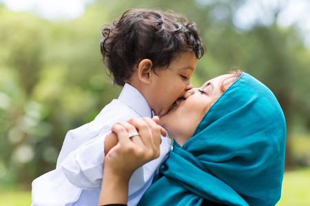 femmes muslim: m�re musulman embrassant son b�b� pr�s Banque d'images