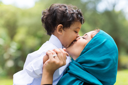 mom and son: muslim mother kissing her baby boy close up