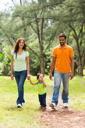 happy young indian family walking in park photo