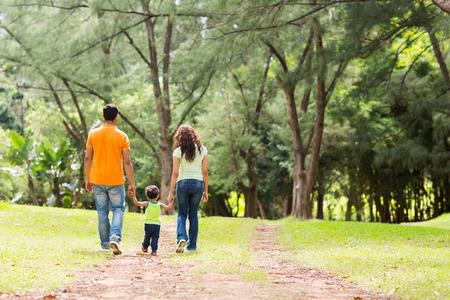 森を歩く手を繋いでいる若い家族の背面図 写真素材