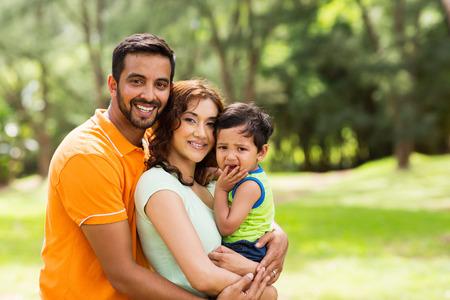 Schöne junge indische Familie draußen schaut in die Kamera