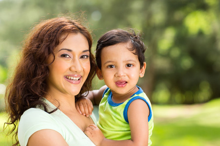 portrait of happy young indian mother and baby boy outdoors