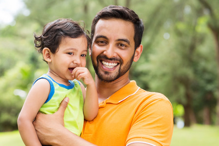 close up portrait of young indian father and baby boy outdoors photo