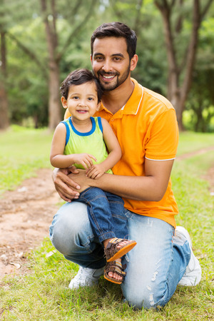 happy indian father and son outdoors in forest photo
