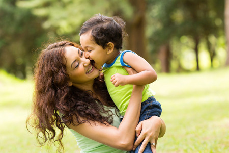 people and nature: happy little indian boy kissing mother outdoors Stock Photo