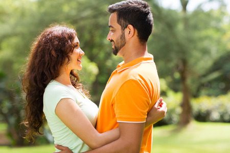 romantic young indian couple hugging outdoors in forest