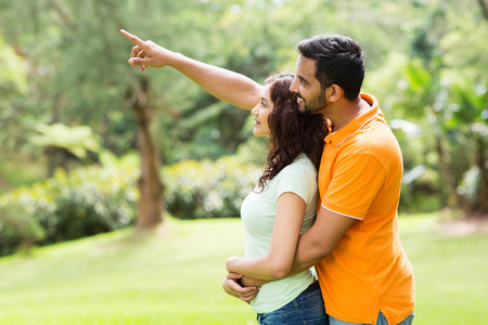 indian summer seasons: loving young indian couple looking and pointing in the forest