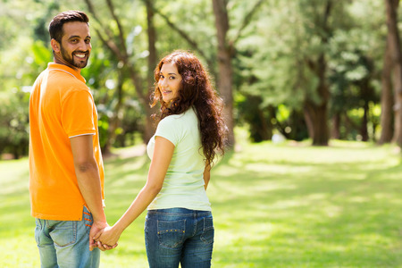 indian summer seasons: cute indian couple holding hands and looking back outdoors Stock Photo