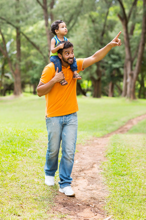 indian happy family: caring young indian father and son walking outdoors in forest Stock Photo