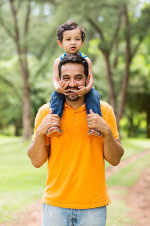 cheerful indian father carrying son on his shoulders in the park photo