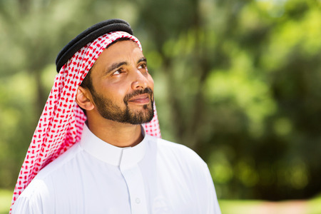 handsome middle eastern man looking up outdoors photo