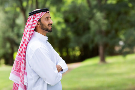 cute arabian man with arms crossed looking away photo