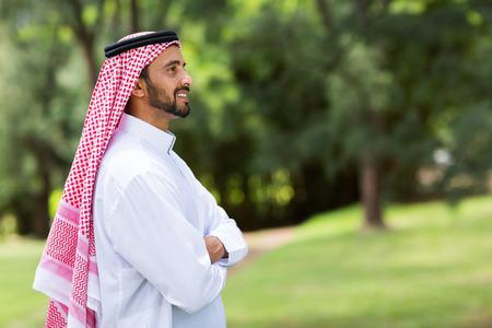 cute arabian man with arms crossed looking away photo