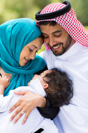 happy middle eastern couple and baby boy outdoors photo