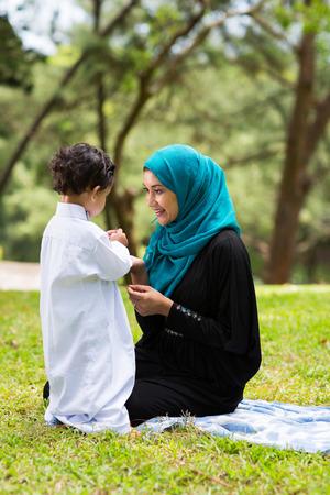 femmes muslim: arabe jouant avec son mignon petit gar�on dans le parc m�re