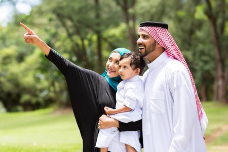 linda familia árabe mira y que señala en el bosque Foto de archivo