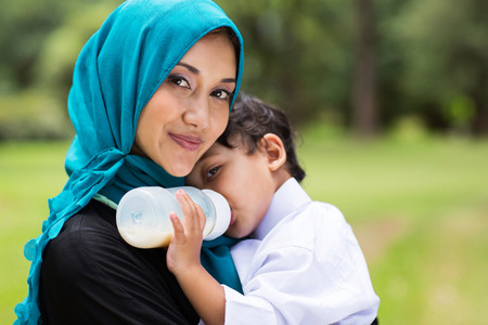 beautiful Arabic mother and baby boy outdoors photo