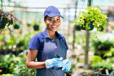 farm worker: pretty african american female gardener in greenhouse