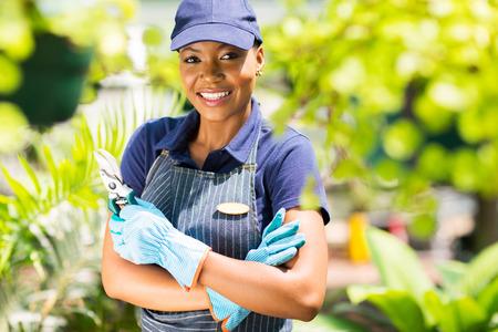 happy african nursery worker holding garden tool photo
