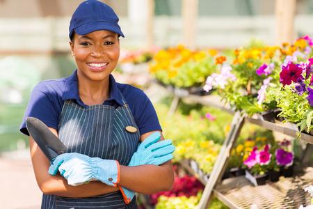 florists: beautiful black nursery worker in greenhouse