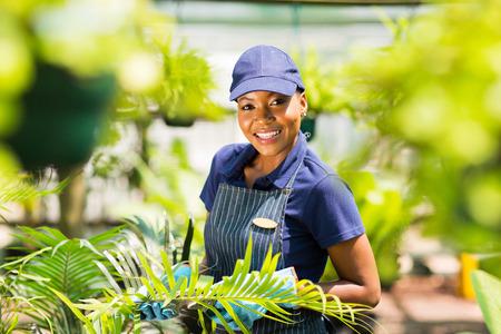 gardening gloves: portrait of young afro american nursery worker gardening