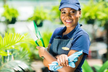 jardinero: Jardinero sonriente que sostiene la herramienta de jardín afroamericano