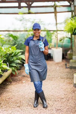 nurser: happy african nurser owner holding a shovel in greenhouse
